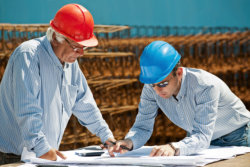 Young engineer shows a senior foreman the next steps in a construction project.